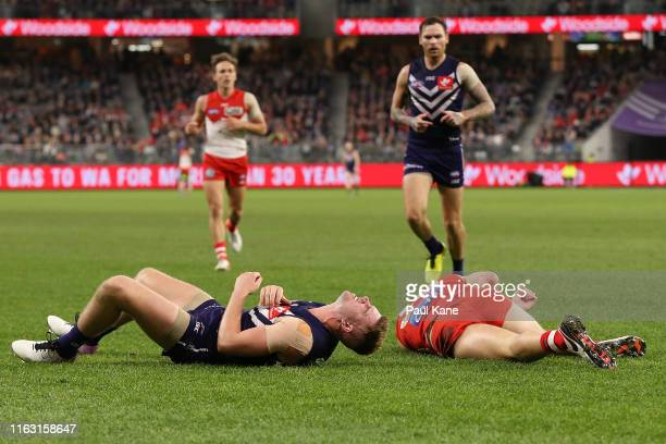 Luke Ryan of the Dockers and Tom McCartin of the Swans lay injured on field following a marking contest during the round 18 AFL match between the...