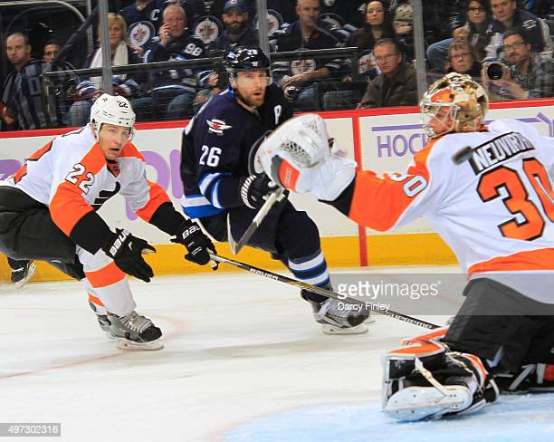 Luke Schenn of the Philadelphia Flyers and Blake Wheeler of the Winnipeg Jets watch as the puck flies past the outstretched glove of goaltender...