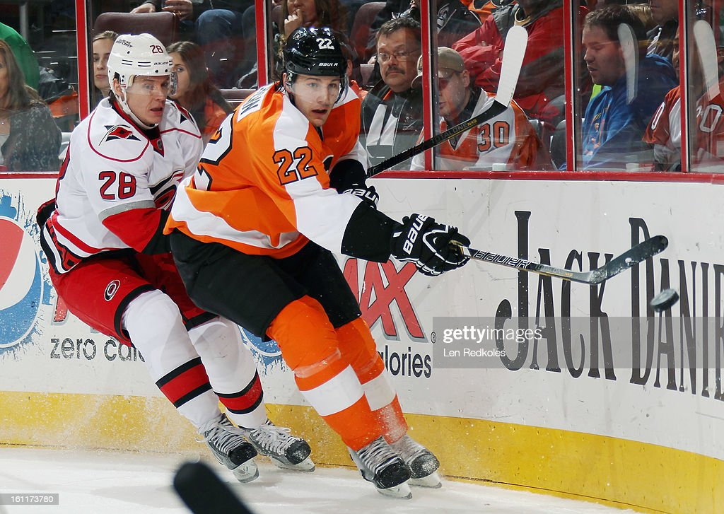 Luke Schenn #22 of the Philadelphia Flyers battles Alexander Semin #28 of the Carolina Hurricanes for the airborn puck on February 9, 2013 at the Wells Fargo Center in Philadelphia, Pennsylvania. The Flyers went on to defeat the Hurricanes 4-3 in OT.