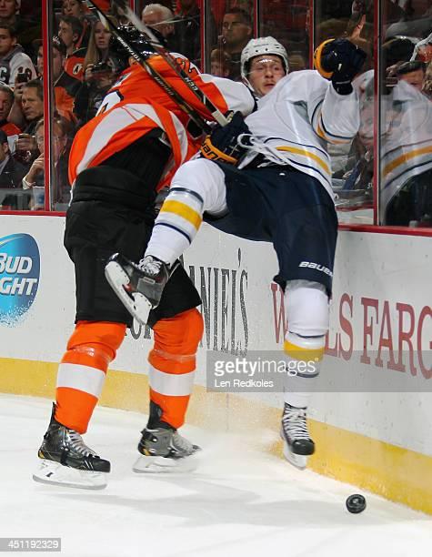 Luke Schenn of the Philadelphia Flyers checks Luke Adam of the Buffalo Sabres into the boards on November 21 2013 at the Wells Fargo Center in...