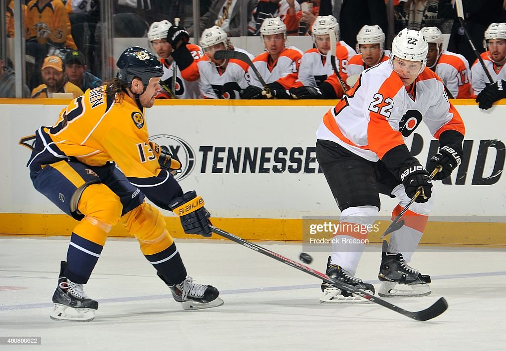 Luke Schenn #22 of the Philadelphia Flyers passes the puck past Olli Jokinen #13 of the Nashville Predators during the first period of a game at Bridgestone Arena on December 27, 2014 in Nashville, Tennessee.