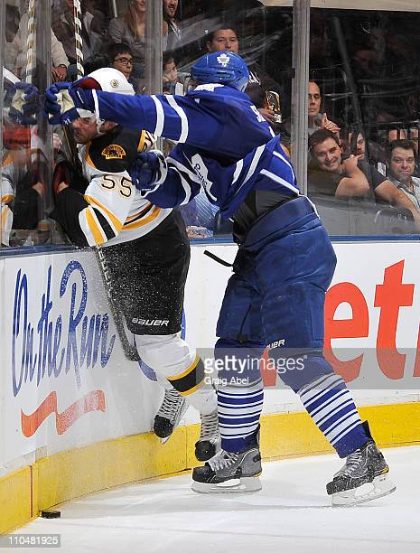 Luke Schenn of the Toronto Maple Leafs checks Johnny Boychuk of the Boston Bruins into the end boards during game action March 19 2011 at the Air...