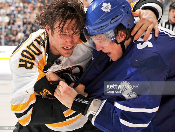 Luke Schenn of the Toronto Maple Leafs fights with Steve Montador of the Boston Bruins during game action March 28 2009 at the Air Canada Centre in...