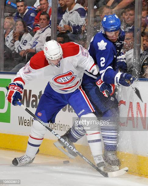 Luke Schenn of the Toronto Maple Leafs is checked into the boards by Benoit Pouliot of the Montreal Canadiens during game action October 7 2010 at...