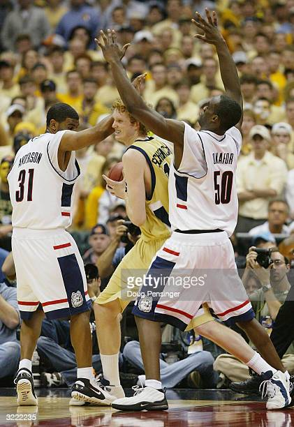 Luke Schenscher of the Georgia Tech Yellow Jackets is guarded by Emeka Okafor and Rashad Anderson of the UConn Huskies during the National...