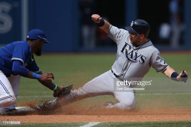 Luke Scott of the Tampa Bay Rays steals second base in the eighth inning during MLB game action as Jose Reyes of the Toronto Blue Jays applies the...