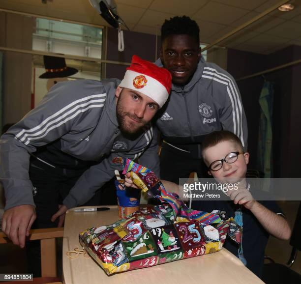 Luke Shaw and Axel Tuanzebe of Manchester United deliver Christmas presents to Brandon during the club's annual Christmas hospital visits at Royal...