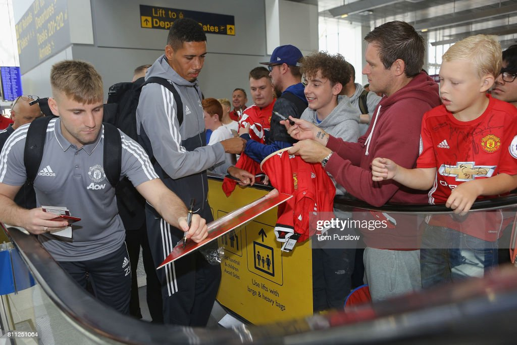 Luke Shaw and Chris Smalling of Manchester United sign autographs at Manchester Airport ahead of the club's pre-season tour of the USA at Manchester Airport on July 9, 2017 in Manchester, England.