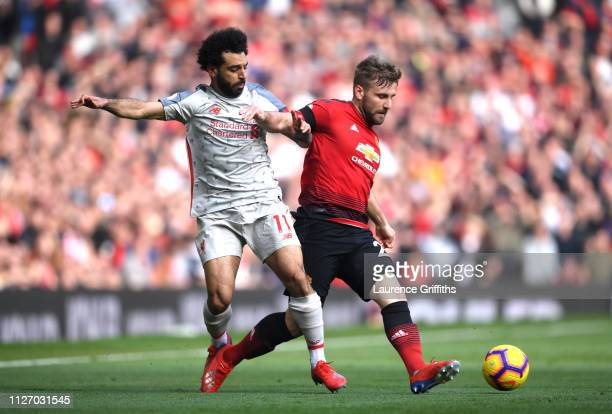 Luke Shaw of Manchester United battles for possession with Mohamed Salah of Liverpool during the Premier League match between Manchester United and...