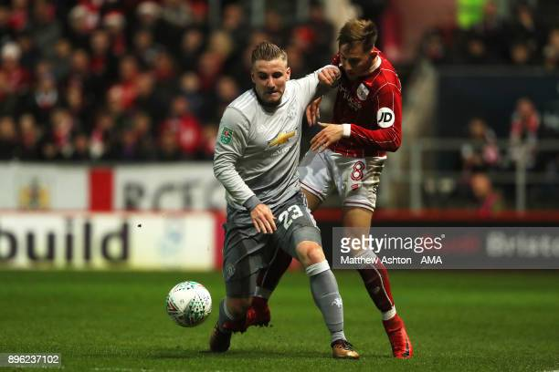 Luke Shaw of Manchester United competes with Josh Brownhill of Bristol City during the Carabao Cup QuarterFinal match between Bristol City and...