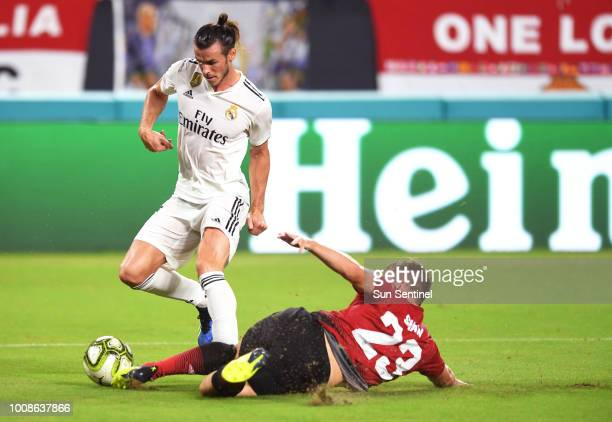 Luke Shaw of Manchester United makes a sliding tackle on Gareth Bale of Real Madrid in the first half during International Champions Cup action at...