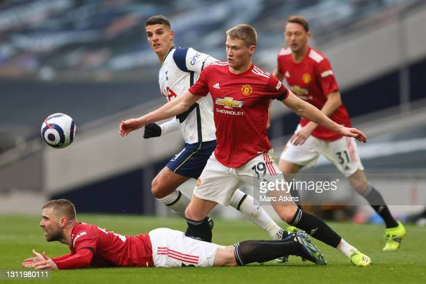 Luke Shaw of Manchester United reacts on the ground as Erik Lamela of Tottenham Hotspur and Scott McTominay of Manchester United battle for...