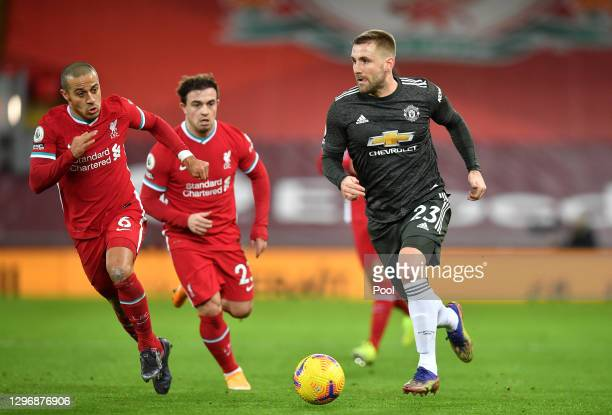 Luke Shaw of Manchester United runs with the ball whilst being closed down by Thiago Alcantara of Liverpool during the Premier League match between...