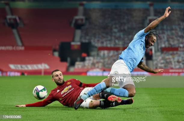 Luke Shaw of Manchester United tackles Raheem Sterling of Manchester City during the Carabao Cup Semi Final match between Manchester United and...