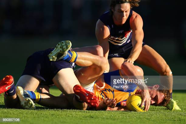 Luke Shuey of the Eagles gets tackled by Andrew Brayshaw and Ed Langdon of the Dockers during the JLT Community Series AFL match between the...