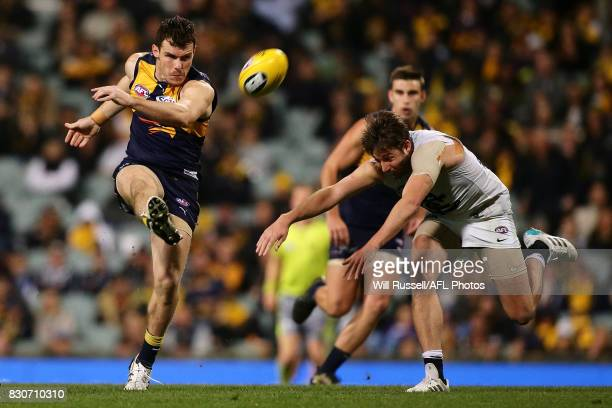 Luke Shuey of the Eagles kicks the ball under pressure from Dale Thomas of the Blues during the round 21 AFL match between the West Coast Eagles and...