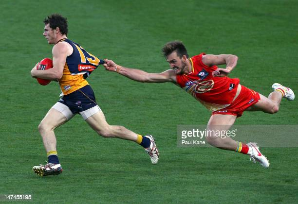 Luke Shuey of the Eagles looks to break clear of Charlie Dixon of the Suns during the round 14 AFL match between the West Coast Eagles and the Gold...