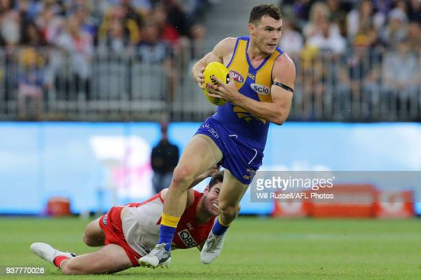 Luke Shuey of the Eagles looks to pass the ball under pressure from George Hewett of the Swans during the round one AFL match between the West Coast...