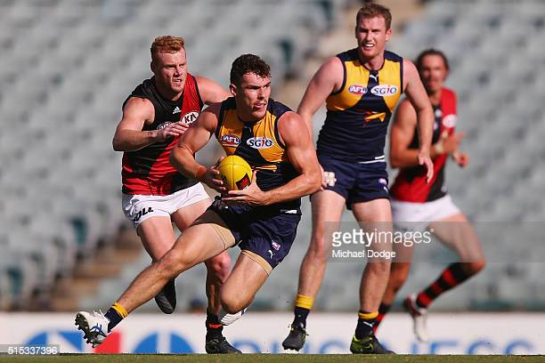 Luke Shuey of the Eagles runs with the ball ahead of Adam Cooney of the bombers during the NAB Challenge AFL match between the West Coast Eagles and...