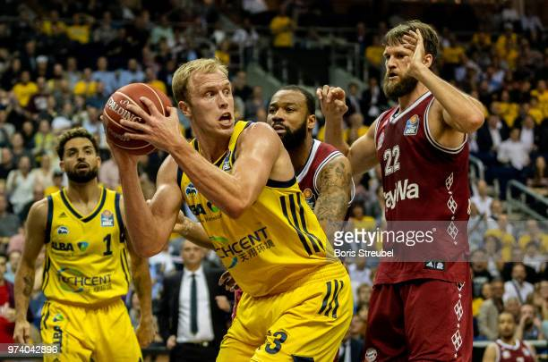 Luke Sikma of ALBA Berlin competes with Danilo Barthel of Bayern Muenchen during the fourth play-off game of the German Basketball Bundesliga finals...