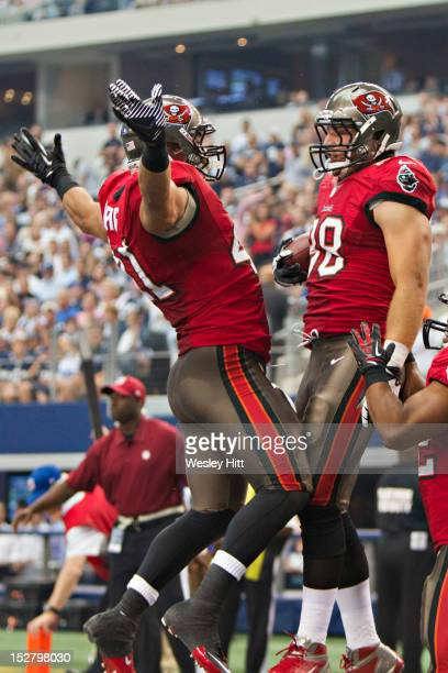 Luke Stocker and Erik Lorig of the Tampa Bay Buccaneers bump chest in celebration after a touchdown against the Dallas Cowboys at Cowboys Stadium on...