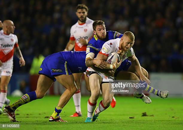 Luke Thompson of St Helens is tackled by Daryl Clark of Warrington Wolves during the First Utility Super League Semi Final match between Warrington...