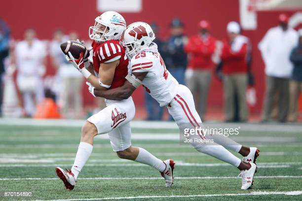 Luke Timian of the Indiana Hoosiers gets hit after a catch against Derrick Tindal of the Wisconsin Badgers in the first quarter of a game at Memorial...
