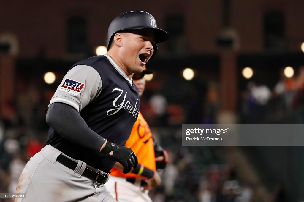 Luke Voit #45 of the New York Yankees celebrates as he runs the bases after hitting a two-run home run in the tenth inning against the Baltimore Orioles at Oriole Park at Camden Yards on August 24, 2018 in Baltimore, Maryland.