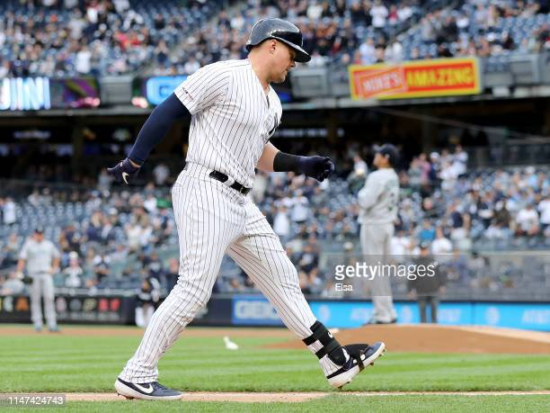Luke Voit of the New York Yankees celebrates his two run home run as Felix Hernandez of the Seattle Mariners looks on in the first inning at Yankee...