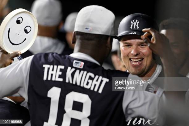 Luke Voit of the New York Yankees celebrates in the dugout after hitting a two run home run with teammate Didi Gregorius against the Baltimore...