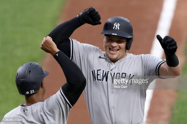 Luke Voit of the New York Yankees celebrates with Aaron Hicks after hitting a first inning grand slam against the Baltimore Orioles at Oriole Park at...