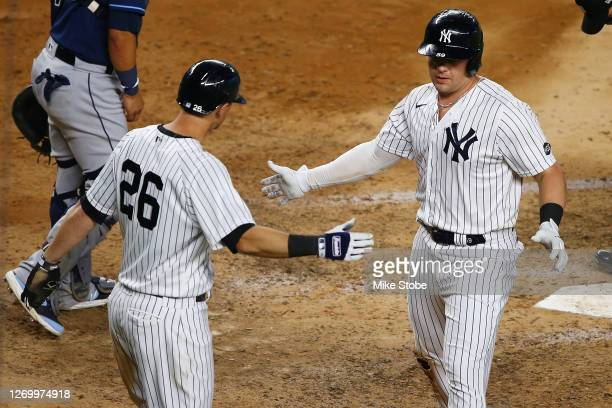 Luke Voit of the New York Yankees celebrates with DJ LeMahieu after hitting a 2-run home run to left field in the eighth inning against the Tampa Bay...