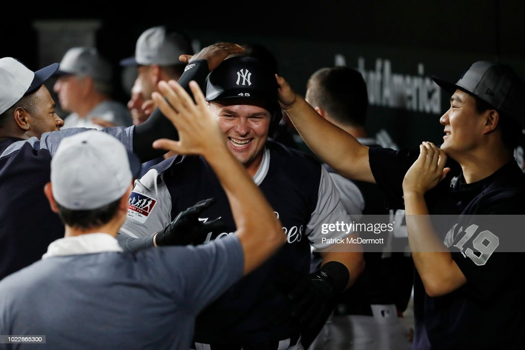 Luke Voit #45 of the New York Yankees celebrates with his teammates in the dugout after hitting a two-run home run in the tenth inning against the Baltimore Orioles at Oriole Park at Camden Yards on August 24, 2018 in Baltimore, Maryland.