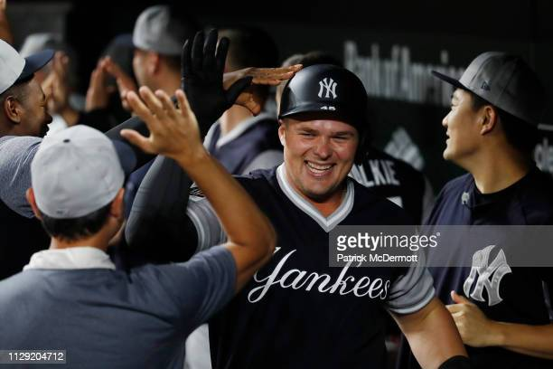 Luke Voit of the New York Yankees celebrates with his teammates in the dugout after hitting a tworun home run in the tenth inning against the...
