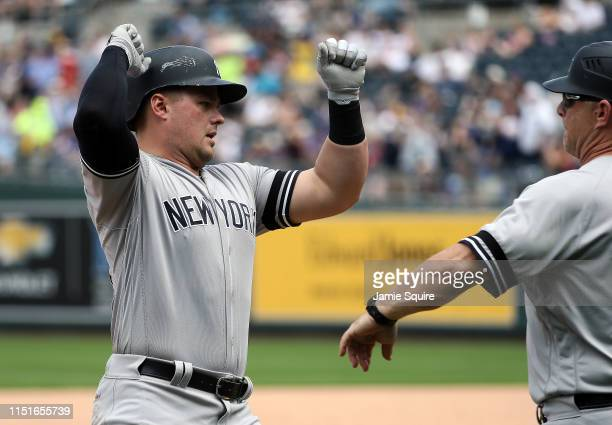 Luke Voit of the New York Yankees celebrates with third base coach Phil Nevin as he rounds the bases after hitting a tworun home run during the 7th...