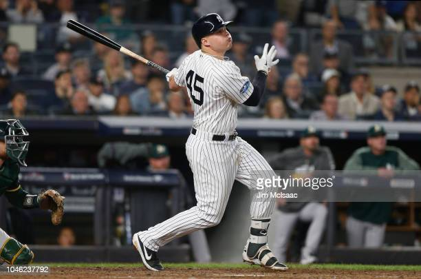 Luke Voit of the New York Yankees follows through on a sixth inning two run triple against the Oakland Athletics in the American League Wild Card...