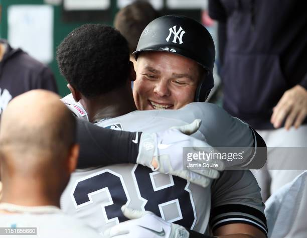 Luke Voit of the New York Yankees is congratulated by Cameron Maybin in the dugout after hitting s tworun home run during the 7th inning of the game...