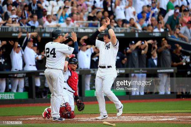 Luke Voit of the New York Yankees is congratulated by Gary Sanchez after scoring on a first inning double hit by Didi Gregorius during game one of...