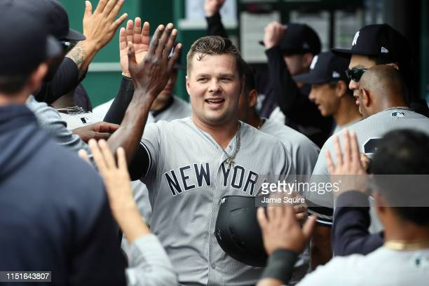 Luke Voit of the New York Yankees is congratulated by teammates in the dugout after scoring during the 1st inning of the game against the Kansas City...