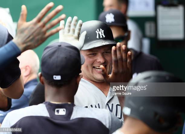 Luke Voit of the New York Yankees is congratulated by teammates in the dugout after hitting s tworun home run during the 7th inning of the game...