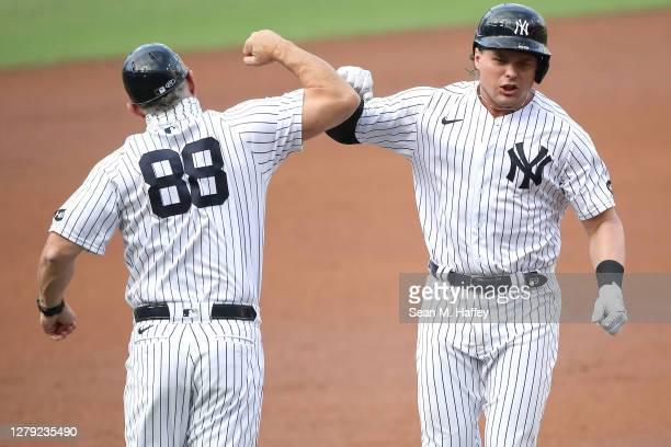 Luke Voit of the New York Yankees is congratulated by third base coach Phil Nevin after hitting a solo home run against the Tampa Bay Rays during the...