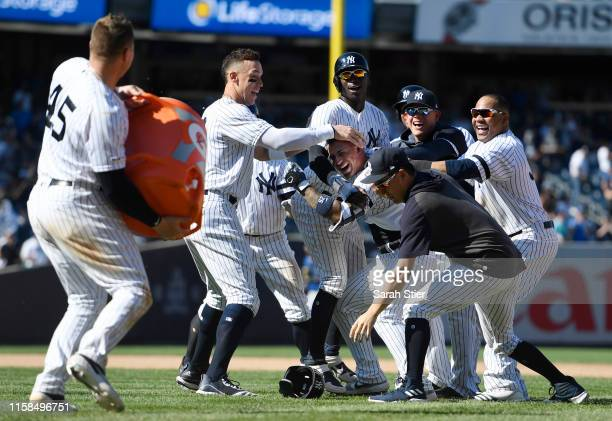 Luke Voit of the New York Yankees prepares to throw a bucket of water on Gleyber Torres after Torres' walk-off single during the ninth inning of the...
