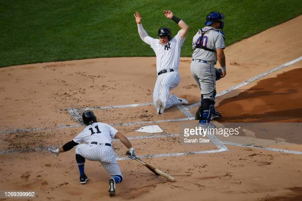Luke Voit of the New York Yankees slides into home past Wilson Ramos of the New York Mets as teammate Brett Gardner signals during the first inning...