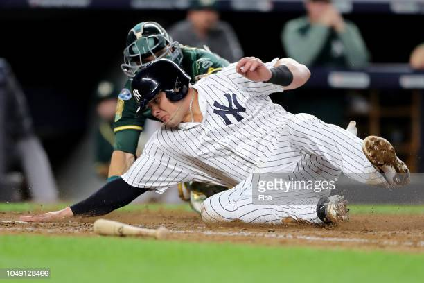 Luke Voit of the New York Yankees slides into home plate against Jonathan Lucroy of the Oakland Athletics to score a run off of Didi Gregorius sac...