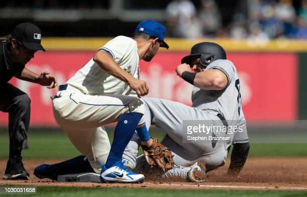 Luke Voit of the New York Yankees slides safely into third base ahead of a tag by third baseman Kristopher Negron of the Seattle Mariners on a by...