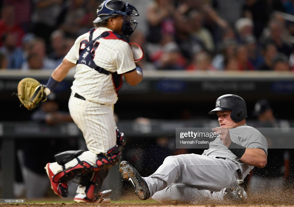 Luke Voit #45 of the New York Yankees slides safely past Willians Astudillo #64 of the Minnesota Twins to score a run during the eighth inning of the game on September 12, 2018 at Target Field in Minneapolis, Minnesota. The Twins defeated the Yankees 3-1.