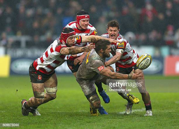 Luke Wallace of Quins passes the ball as the Gloucester defence gang up to bring him down during the Aviva Premiership match between Gloucester Rugby...