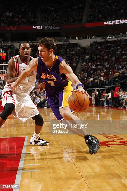 Luke Walton of the Los Angeles Lakers drives to the basket around Tracy McGrady of the Houston Rockets during a game at the Toyota Center on January...