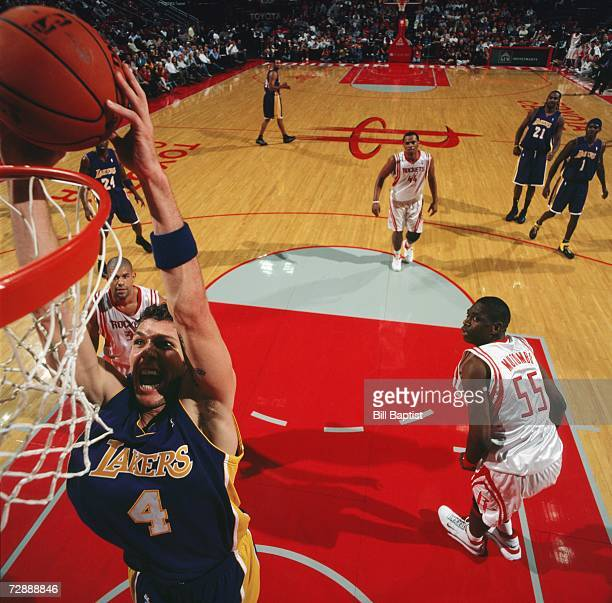 Luke Walton of the Los Angeles Lakers takes the ball to the basket past Dikembe Mutombo of the Houston Rockets during game at Toyota Center on...