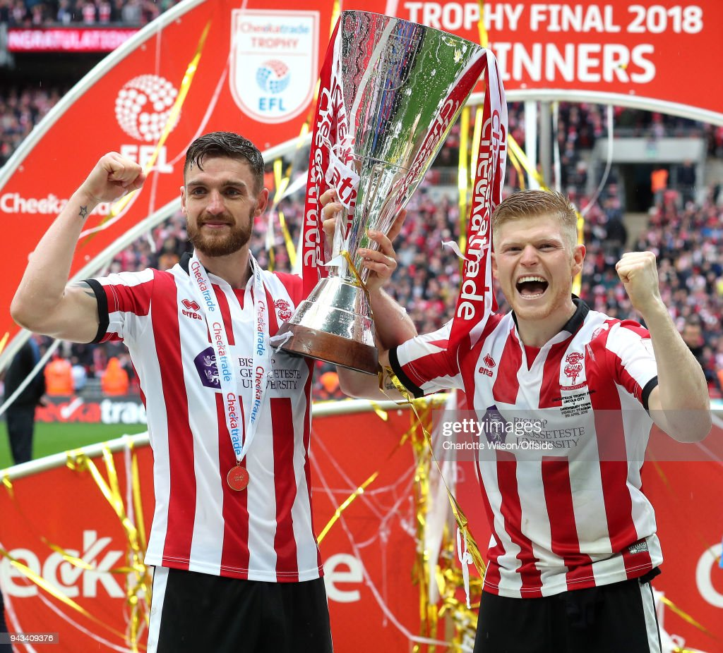 Luke Waterfall and goalscorer Elliot Whitehouse of Lincoln celebrate with the trophy during the Checkatrade Trophy Final between Lincoln City and Shrewsbury Town at Wembley Stadium on April 8, 2018 in London, England.